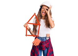 Young hispanic woman with tattoo wearing architect hardhat holding build project smiling happy doing ok sign with hand on eye looking through fingers