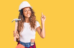 Young hispanic woman with tattoo wearing hardhat and builder clothes holding hammer surprised with an idea or question pointing finger with happy face, number one