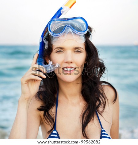Young hispanic woman with wet skin and with a snorkel standing on beach after going to swim in clear mediterranean sea