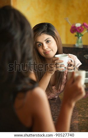 Young Hispanic women with coffee chat in kitchen