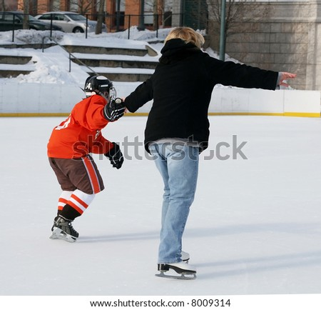 young hockey player helping mom ice skate