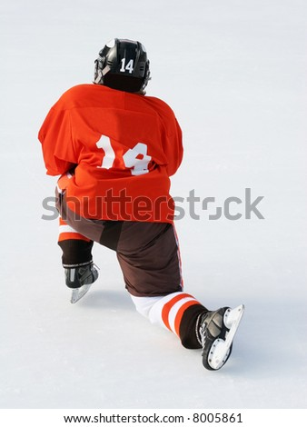 young hockey player resting on ice