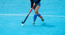 Young hockey player woman with ball in attack playing field hockey game. Horizontal sport poster, greeting cards, headers, website