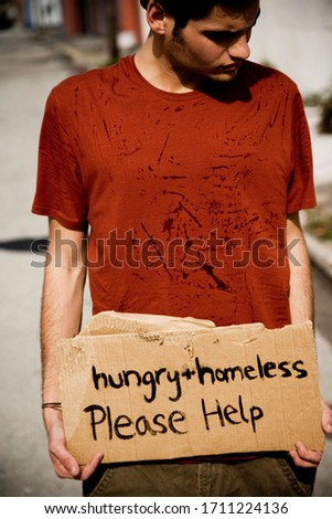 Young homeless man holding sign