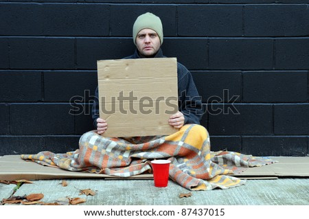 Young homeless man holds blank cardboard for your own text