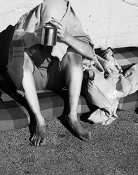 young homeless with filthy dirty feet asking for charity covered with a blanket with black and white effect to emphasize the social drama