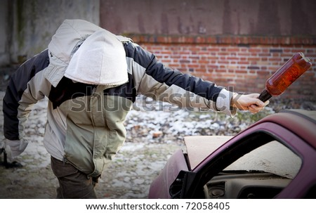 Young hooligan smashing windshield