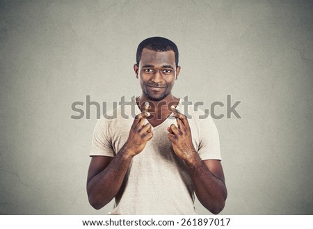 Young hopeful man crossing fingers isolated on grey wall background. Human face expression