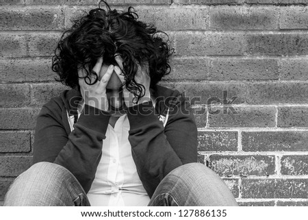 Young hopeless woman sitting against wall