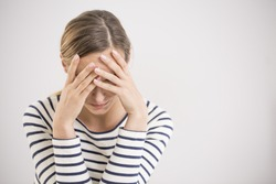Young hopeless woman suffering from depression having nervous breakdown holding her head on isolated background, copy space