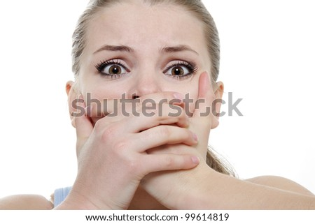 young horrified woman closing her mouth with hands over white