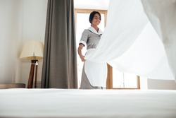 Young hotel maid changing bed sheets