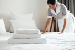 Young hotel maid making the bed with clean fresh towels