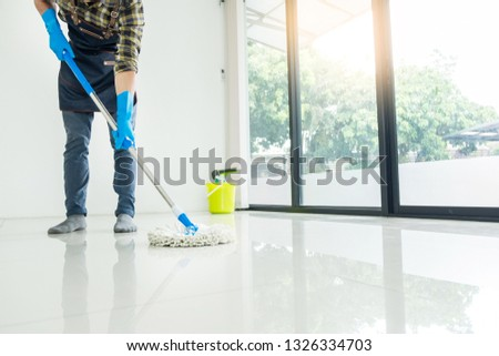 Young housekeeper cleaning floor mobbing holding mop and plastic bucket with brushes, gloves and detergents in the leaving room house floor helping his wife #1326334703