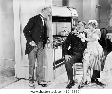 Young housekeeper sitting on the lap of her lover in the kitchen