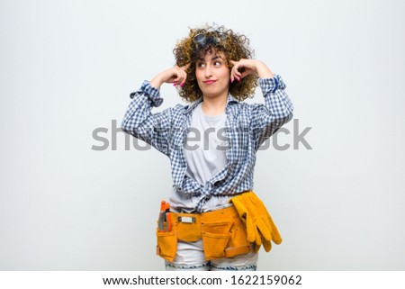 young housekeeper woman feeling confused or doubting, concentrating on an idea, thinking hard, looking to copy space on side against white wall