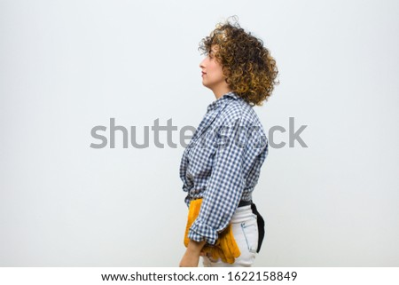 young housekeeper woman on profile view looking to copy space ahead, thinking, imagining or daydreaming against white wall