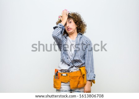 young housekeeper woman raising palm to forehead thinking oops, after making a stupid mistake or remembering, feeling dumb against white wall