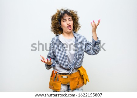 young housekeeper woman shrugging with a dumb, crazy, confused, puzzled expression, feeling annoyed and clueless against white wall