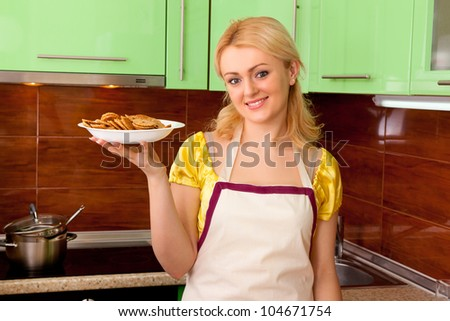 Young housewife cooked meal in kitchen interior