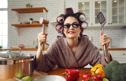 Young housewife cooking at home. Wife waiting for husband sitting at kitchen table. Portrait of funny woman in curlers and thug life 8 bit pixel sunglasses holding meat hammer and spatula and smirking