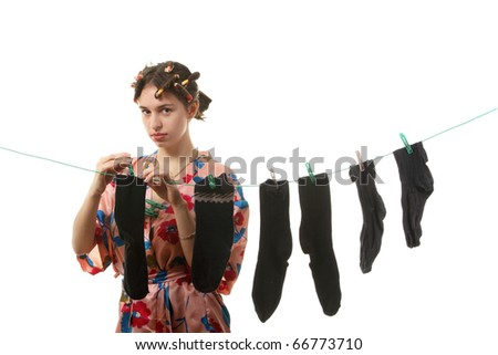 Young housewife hangs up socks on  the clothesline