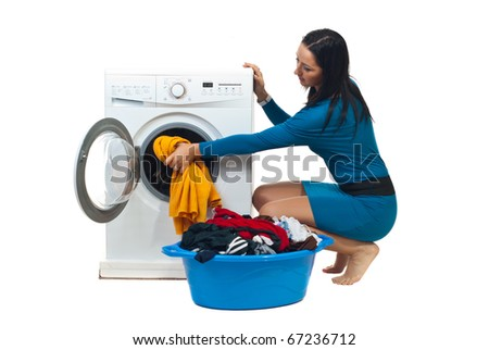 Young housewife in blue dress loading washing machine isolated on white background