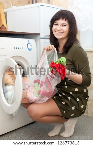 Young housewife loading the washing machine with laundry bag in kitchen