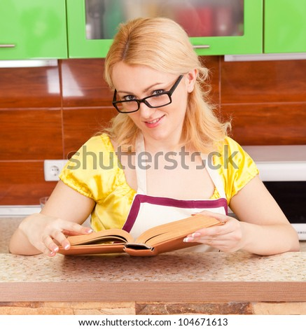 young housewife with a book of recipes in the kitchen