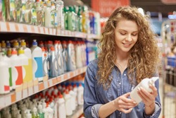 Young housewife with pretty attractive look, chooses household products or detergent for cleaning house in supermarket in washing agent department. Woman holds bottle with washer, reads instruction
