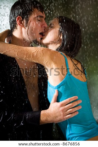 romantic couple kissing in the rain. hugging couple kissing