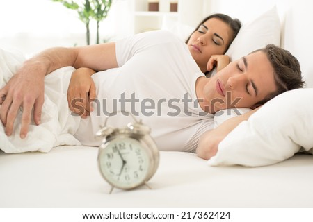 Young hugging couple sleeping on the bed in bedroom
