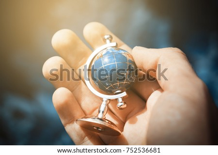 Young human hand is holding small globe with fake color. Nature background. Outdoor. Instagram warm yellow toned. #752536681