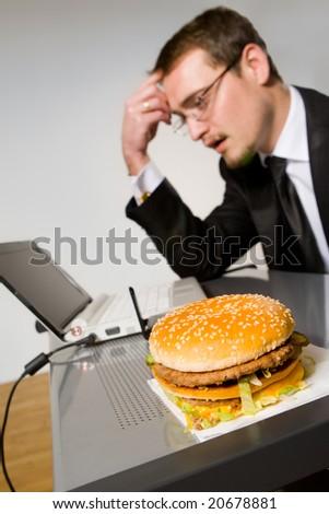 Young hungry businessman eating hamburger