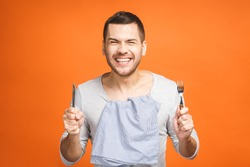Young hungry crazy man holding a fork and a knife. Isolated on orange background.