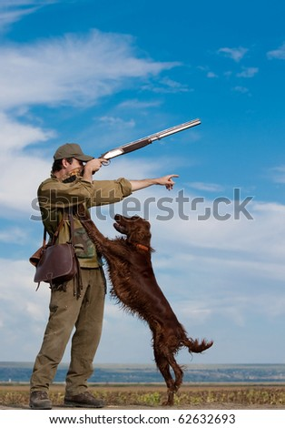 Young hunter training his dog to go for the hunt during a hunting party - stock photo