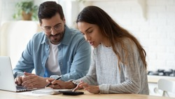 Young husband and wife using calculator laptop computer manage finances calculate bills tax talk doing paperwork together sit at home table discuss family mortgage loan money payment planning budget