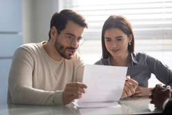 Young husband discussing contract details with smiling wife. Married couple reading carefully terms of conditions of paper document, making decision about house purchase or financial investment.