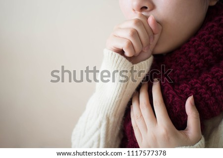 Young ill female have a cough and sore throat in winter. Causes of cough include common cold, flu, respiratory tract infection, pneumonia, bronchitis, allergy, asthma or COPD. Copy space. Health care.