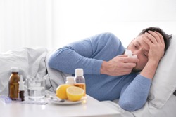 Young ill man lying in bed at home