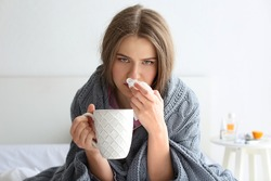Young ill woman with cup of hot tea at home