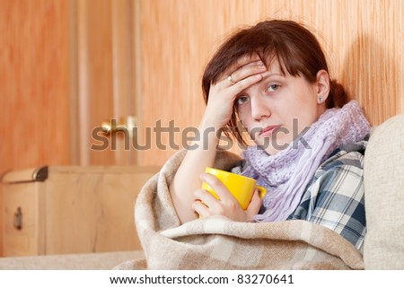 Young illness woman drinking hot tea in blanket
