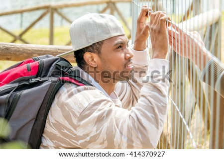 young immigrant holding metal barricade - hand of immigration officer speaking with asylum seeker seeking to cross border enter the country - concept of  illegal immigration and  refugee crisis