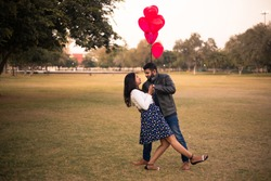 Young Indian Asian Couple Dancing In Garden, spending time together while celebrating Saint Valentine's Day with air balloons in shape of heart in their hand.
