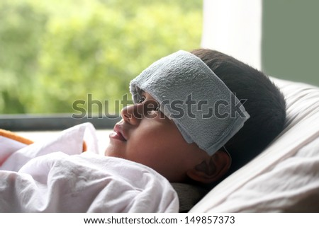 Young indian boy ( child ) down with fever & illness in hospital. A wet cloth is kept on forehead to reduce the temperature