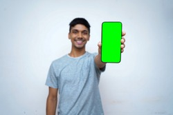 Young indian boy holding a phone with green screen, showing thumbs up in the background.