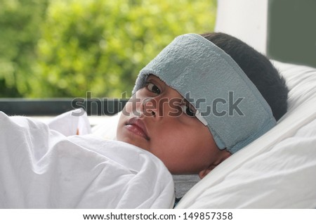 Young indian boy ( kid ) suffering high fever ( flu ) & getting treatment. A wet cloth is kept on forehead to reduce the temperature