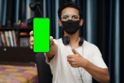 Young indian boy wearing a black mask holding a phone with green screen, showing thumbs up in the background.