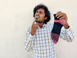 Young Indian businessman holding one stripy socks and thinking for a missing socks. White background