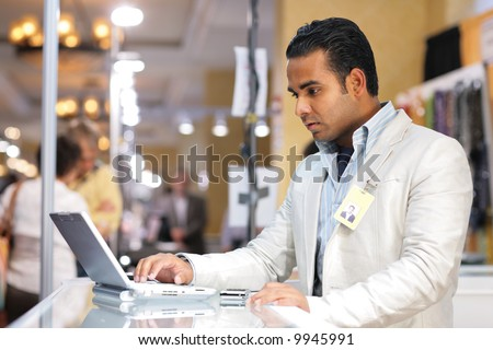 Young indian businessman using laptop computer at trade show.